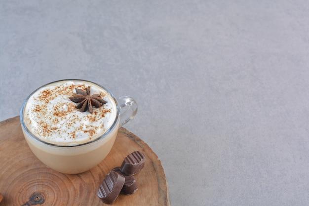 Una taza de café cremoso y canela en rama sobre tablero de madera.
