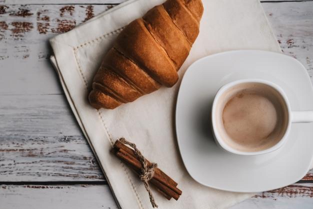 Taza de café y croissant con canela en servilleta sobre una mesa de madera