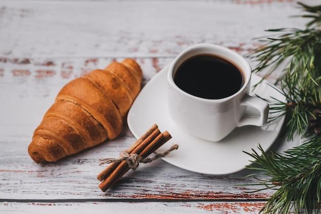 Taza de café y croissant con decoración navideña