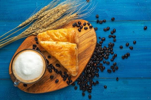 Taza de café y croissant para el desayuno en la superficie de madera azul con granos de café.
