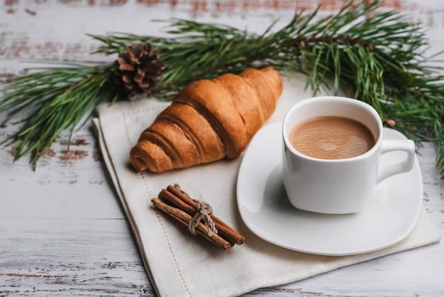 Taza de café y un croissant en la mesa. el concepto de una tarjeta de felicitación navideña