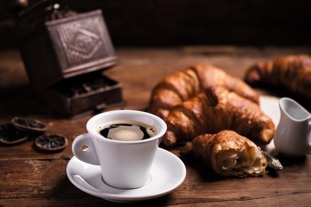 Taza de café con un croissant en una mesa de madera rústica clse up