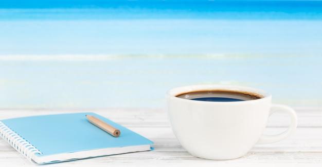 Taza de café y cuaderno azul sobre mesa de madera blanca con fondo de mar brillante