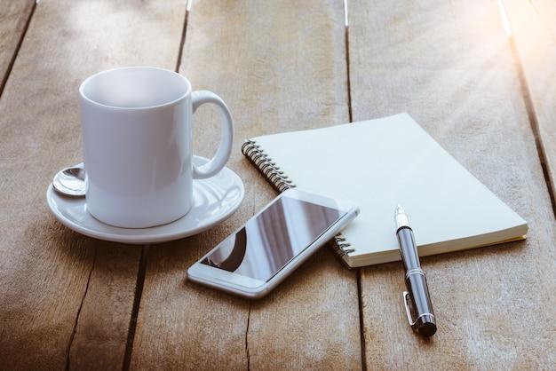 Taza de café, cuaderno, bolígrafo y teléfono inteligente.