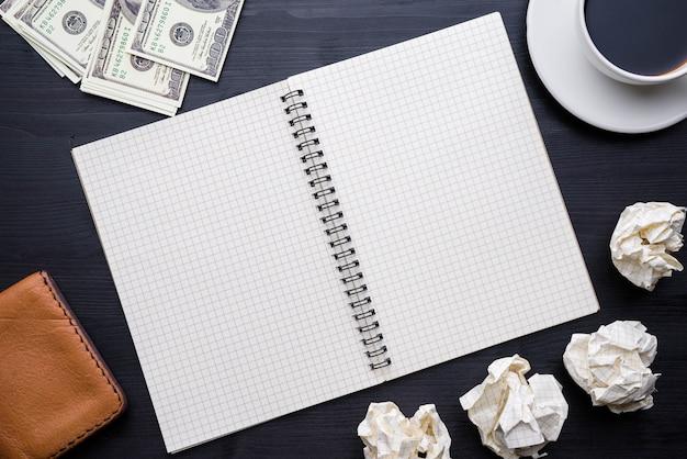 Taza de café y cuaderno en el fondo de la tabla de madera