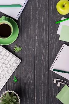 Taza de café con cuaderno y planta suculenta en escritorio de madera