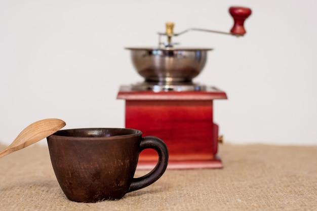 Taza de café y cuchara de madera con molinillo de café manual en el fondo posterior