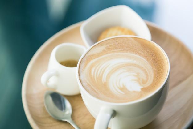Taza de café con un cuenco con galletas y una cucharilla