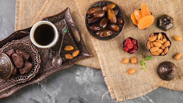 Taza de café con dátiles frutales y almendras en bandeja metálica.