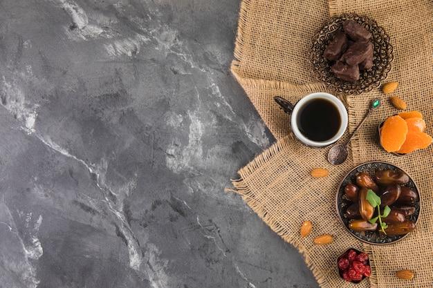 Taza de café con dátiles frutales y almendras.