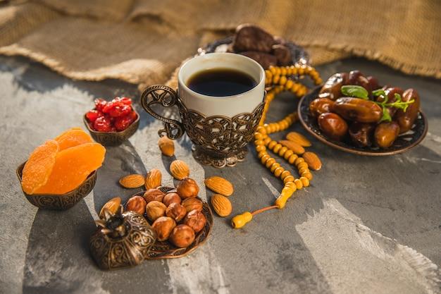 Taza de café con dátiles frutales y diferentes frutos secos.