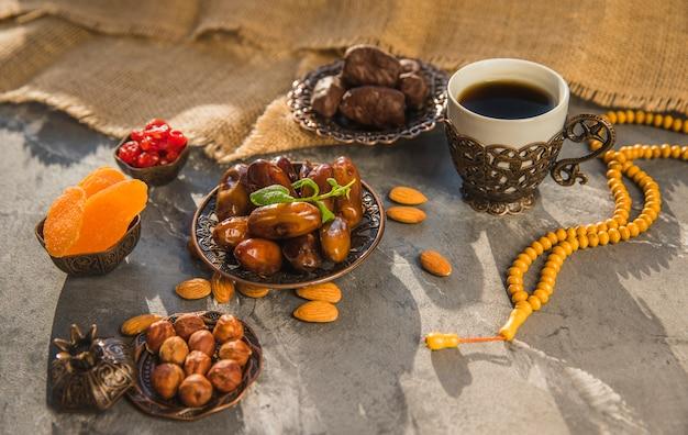 Taza de café con dátiles frutas y frutos secos.