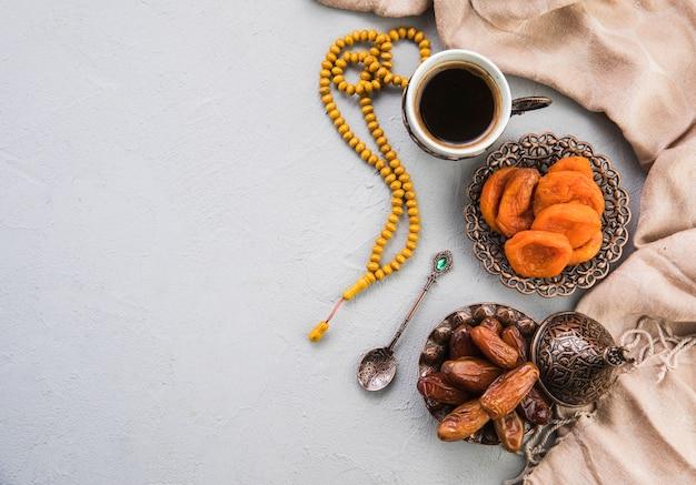 Taza de café con dátiles secos, fruta y albaricoque.
