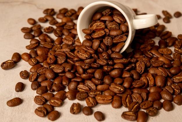 Taza de café derramada con granos tostados