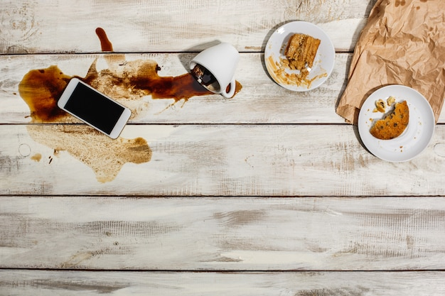 Taza de café derramado sobre la mesa de madera