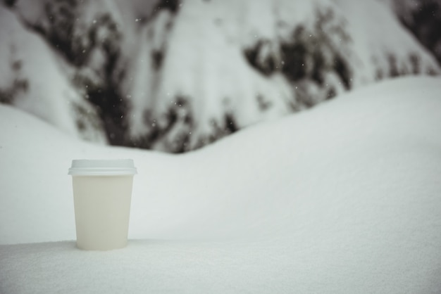 Taza de café desechable en un paisaje nevado