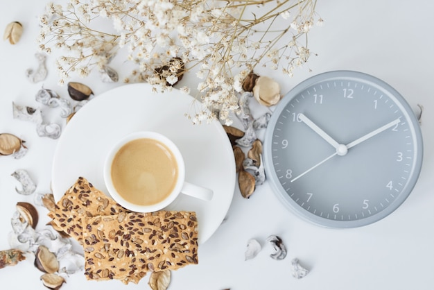 Taza de café y despertador clásico en mesa blanca