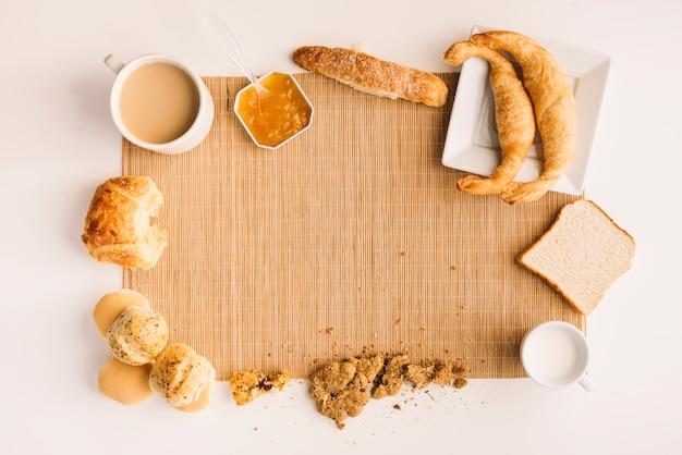 Taza de café con diferente panadería y mermelada en mesa