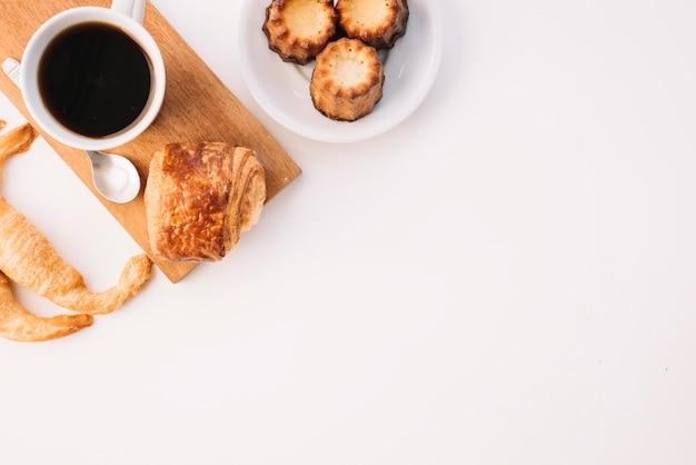 Taza de café con diferente panadería en mesa blanca