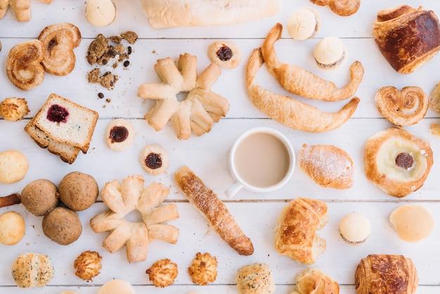 Taza de café con diferente panadería en mesa de madera