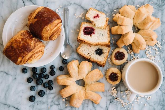 Taza de café con diferente panadería en mesa de mármol
