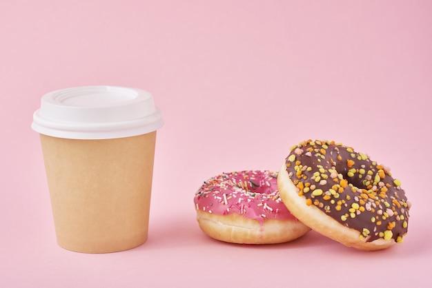 Taza de café y donas en superficie rosa