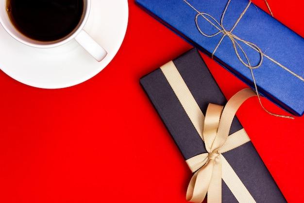 Una taza de café y dos regalos envueltos en papel de regalo azul y negro sobre un fondo rojo.