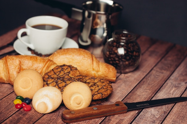 Una taza de café, dulces, galletas, postres, desayuno.