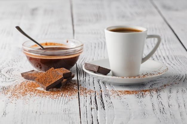 Taza de café y dulces en una mesa blanca