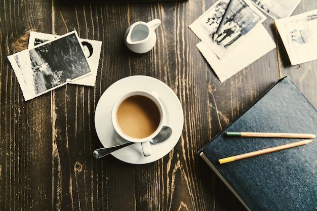 Taza de café se encuentra en la mesa de madera entre todas las fotos