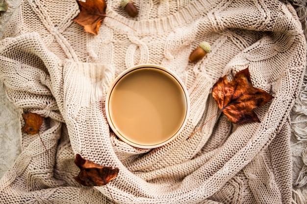 Taza de café envuelta en un suéter beige de lana