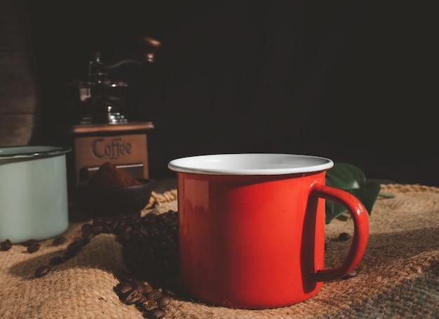 Taza de café de esmalte rojo, café molido, granos de café tostados, molinillo y hojas de monstera en la mesa de madera con fondo de arpillera