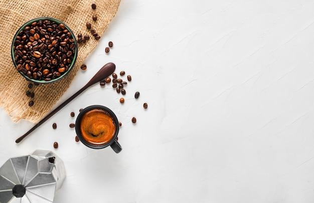 Taza de café con espresso fuerte con espuma, una cafetera y granos de café en un bol