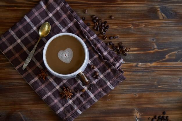 Taza de café con espuma en forma de corazón. con amor por el café. en la mesa de madera copyspace