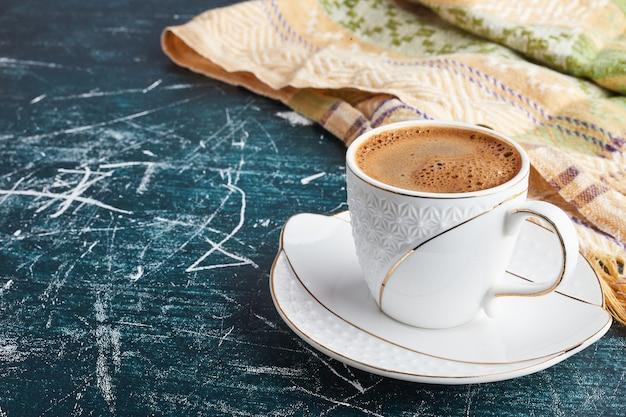 Una taza de café con espuma en un platillo blanco.