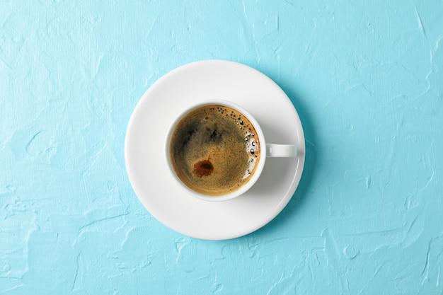 Taza de café con espuma sobre fondo de color