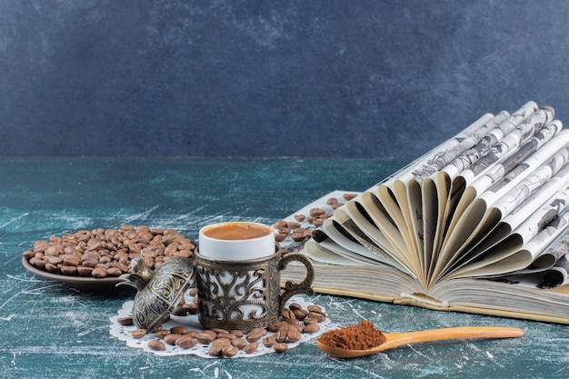 Taza de café espumoso, plato de granos de café y libro sobre mesa de mármol.