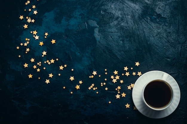 Taza de café y estrellas sobre un fondo azul oscuro. concepto del cielo estrellado y café.