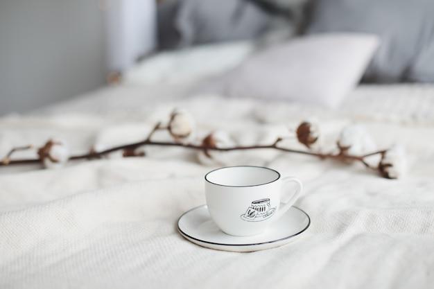 Taza de café y flor de algodón. desayuno en la cama.