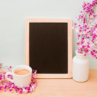 Taza de café y florero rosa para el aliento del bebé cerca de la pizarra de madera en blanco en el escritorio contra la pared