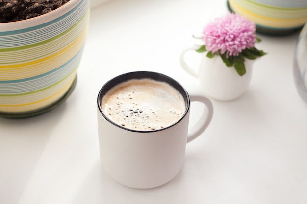 Una taza de café y flores de aster: el concepto de una mañana de primavera o verano, un estilo interior minimalista