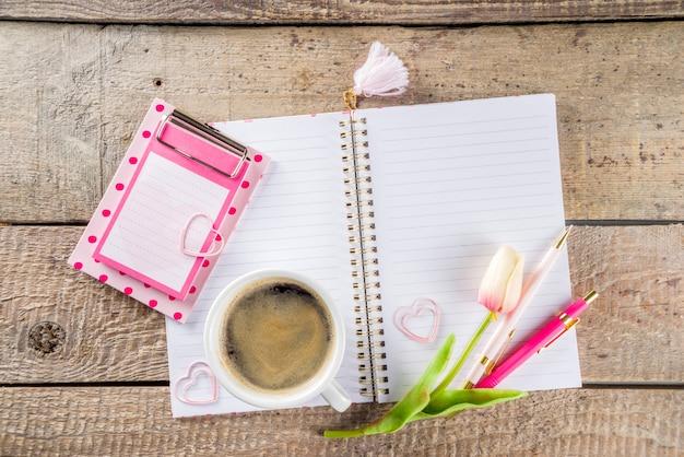 Taza de café con flores y cuaderno de dibujo
