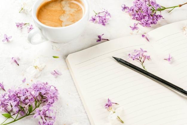 Taza de café, flores y libreta