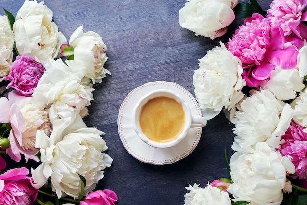 Una taza de café y flores de peonía en madera oscura. vista superior