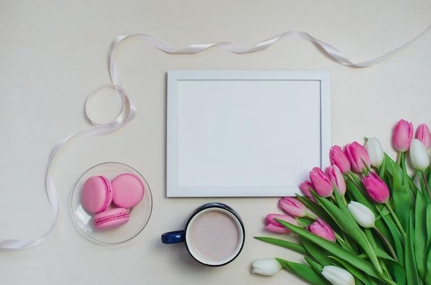 Taza de café, flores de tulipán de primavera y macarons rosados en el fondo de la vista superior de la mesa en colores pastel