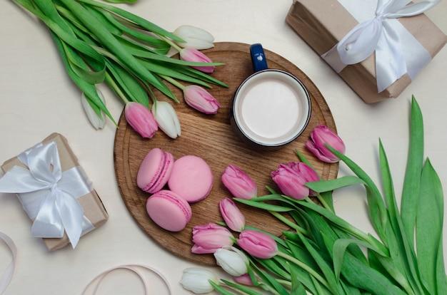 Taza de café, flores de tulipán de primavera y macarons rosados en la vista superior de la mesa en colores pastel.