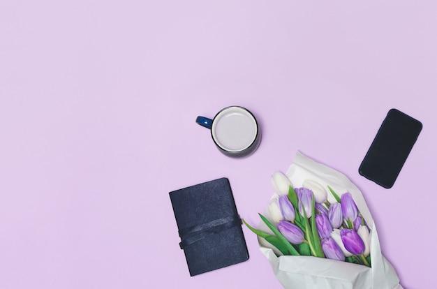 Taza de café, flores de tulipán de primavera y en la mesa. vista superior.