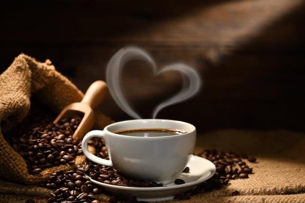 Taza de café con forma de corazón humo y granos de café en saco de arpillera sobre fondo de madera vieja