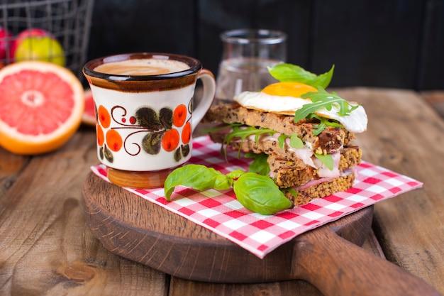 Una taza de café fragante y tostadas con huevo y ensalada para el desayuno.