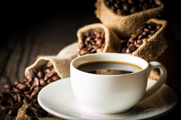 Taza de café y frijoles. café expreso y un pedazo de pastel con un rizo. taza de café y granos de café sobre la mesa.